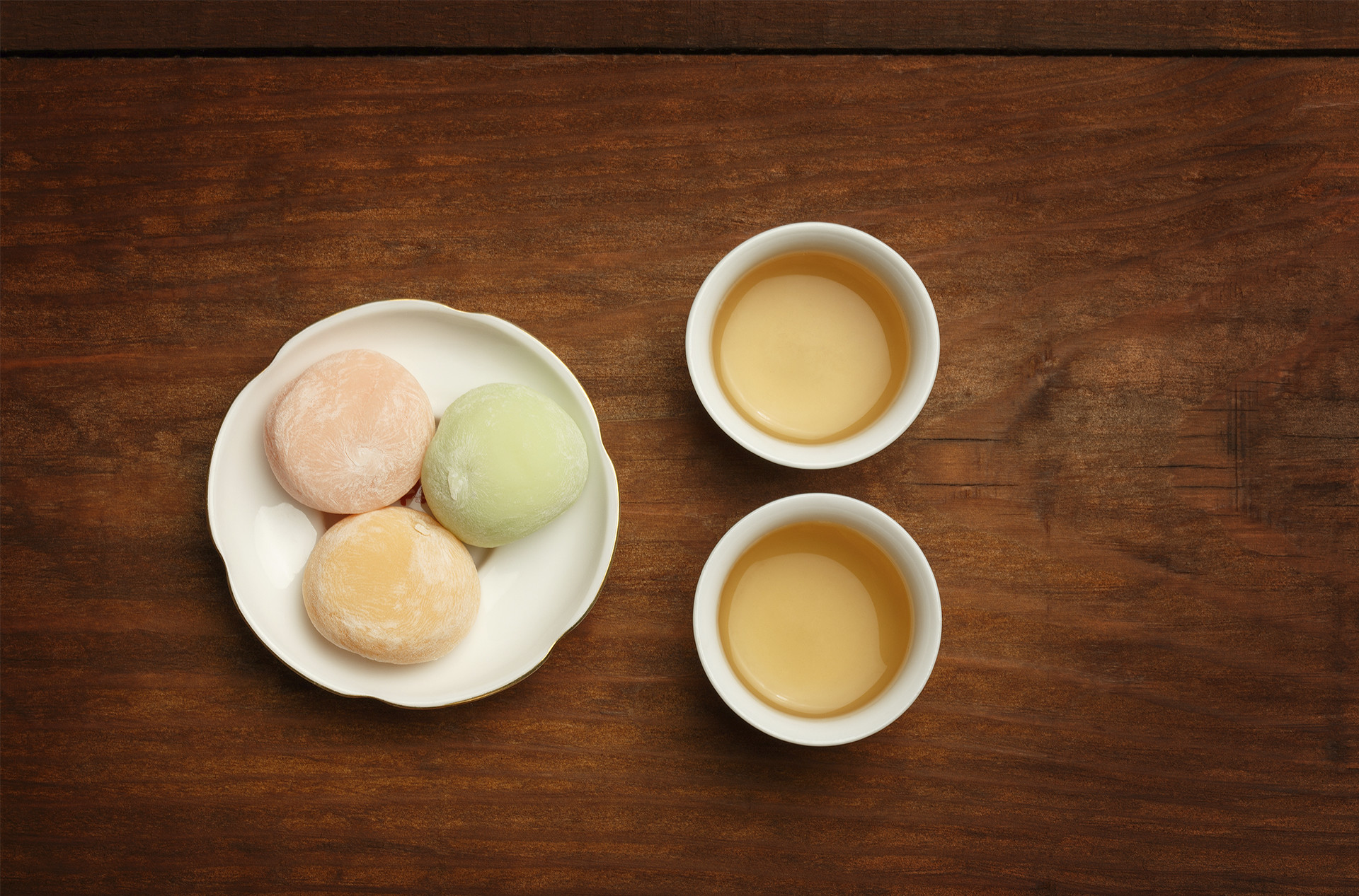 three mochi ice cream balls next to two cups of tea for a tasty pairing
